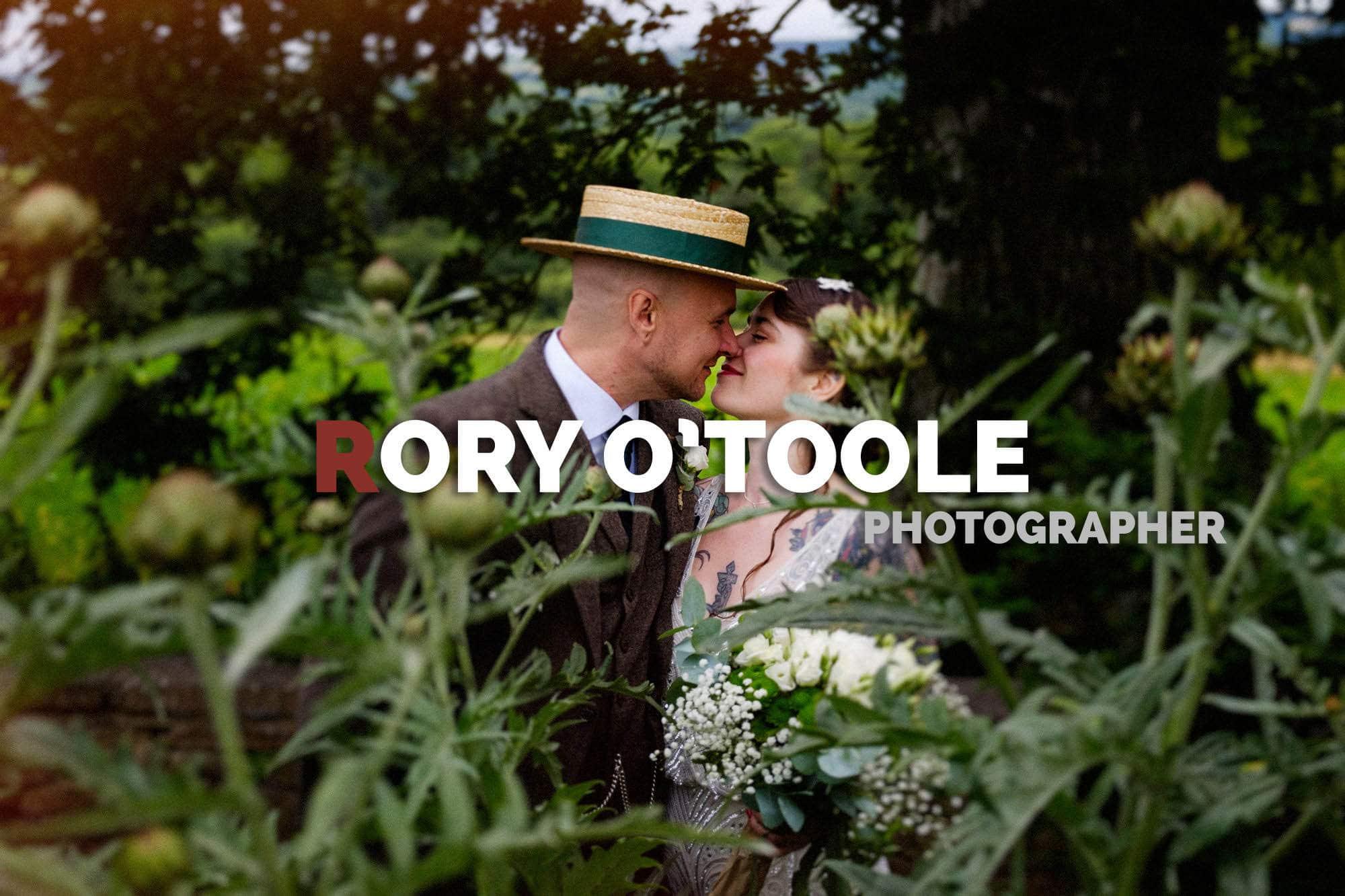 bride and groom kiss behind plants