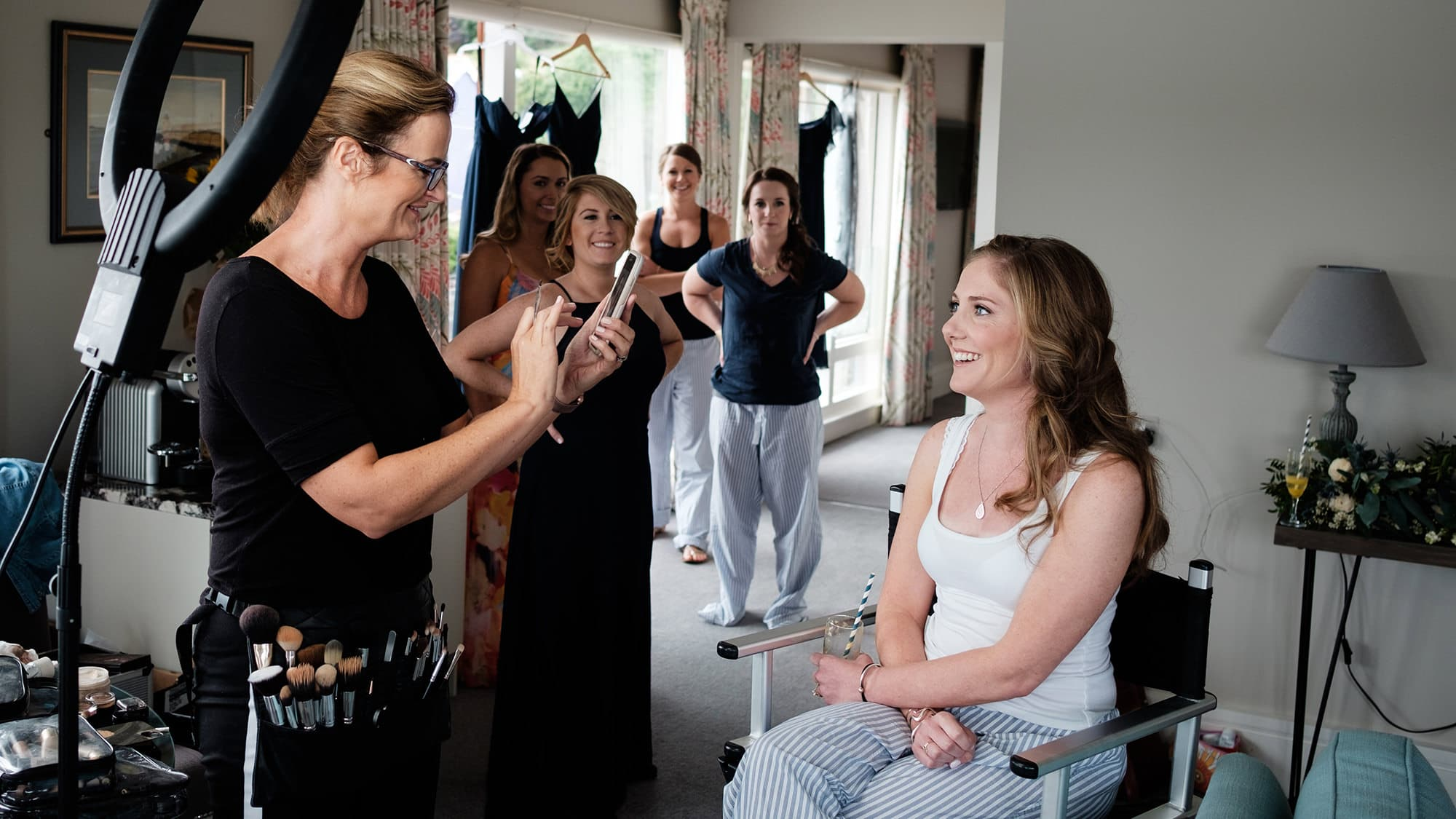 bride getting makeup as bridesmaids look on