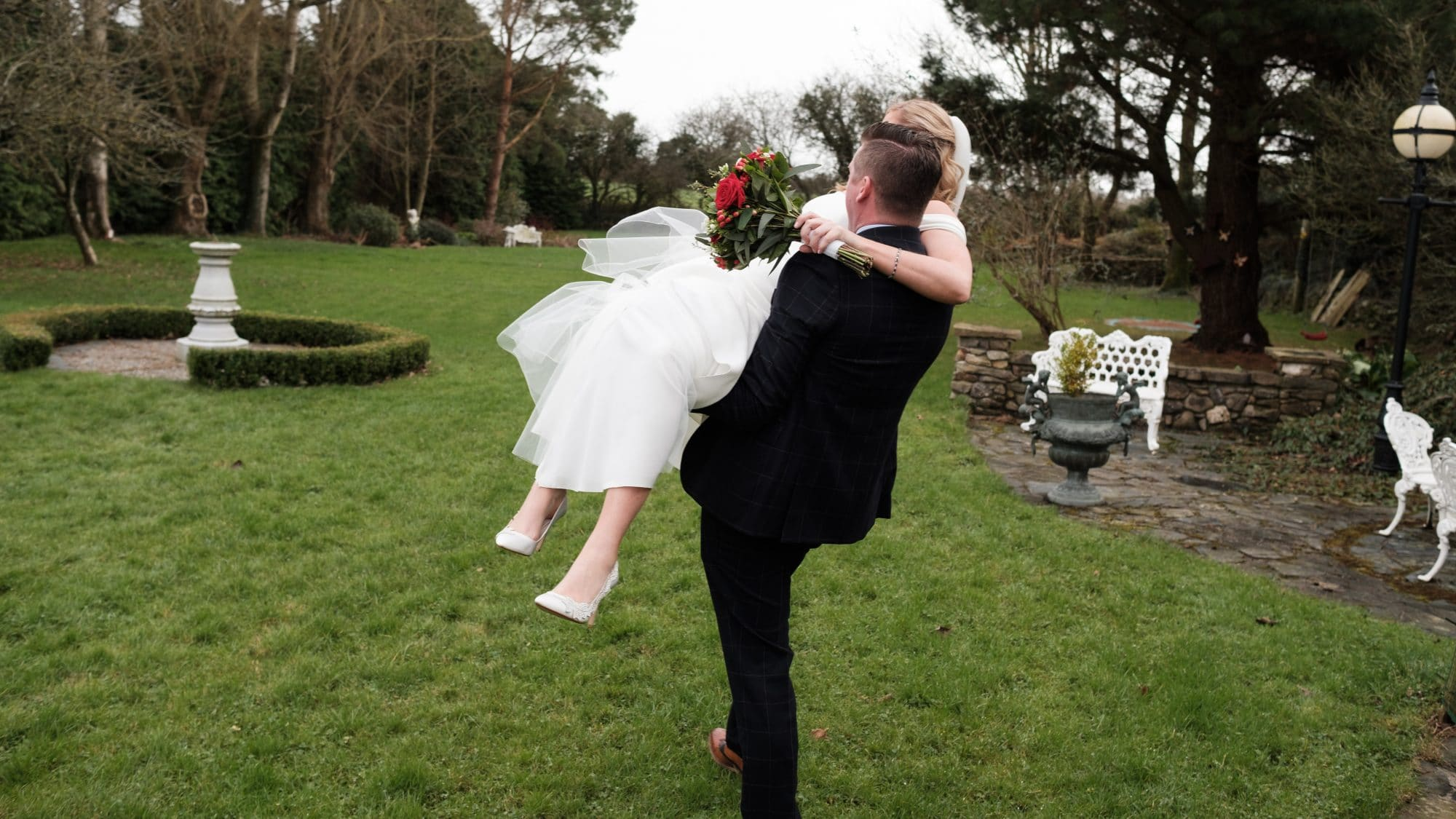 bride being carried across lawn