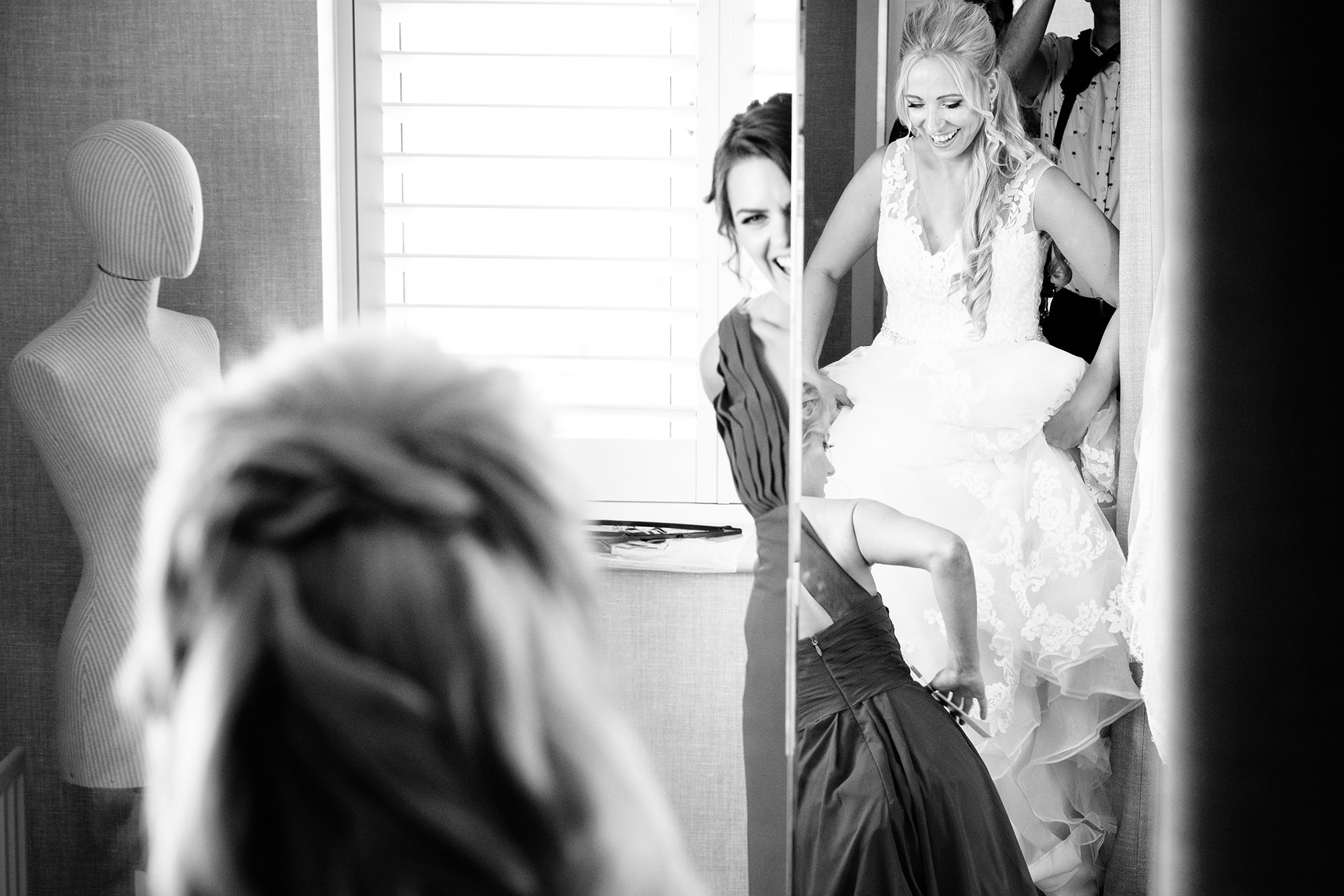 bride and bridesmaids dressing and laughing