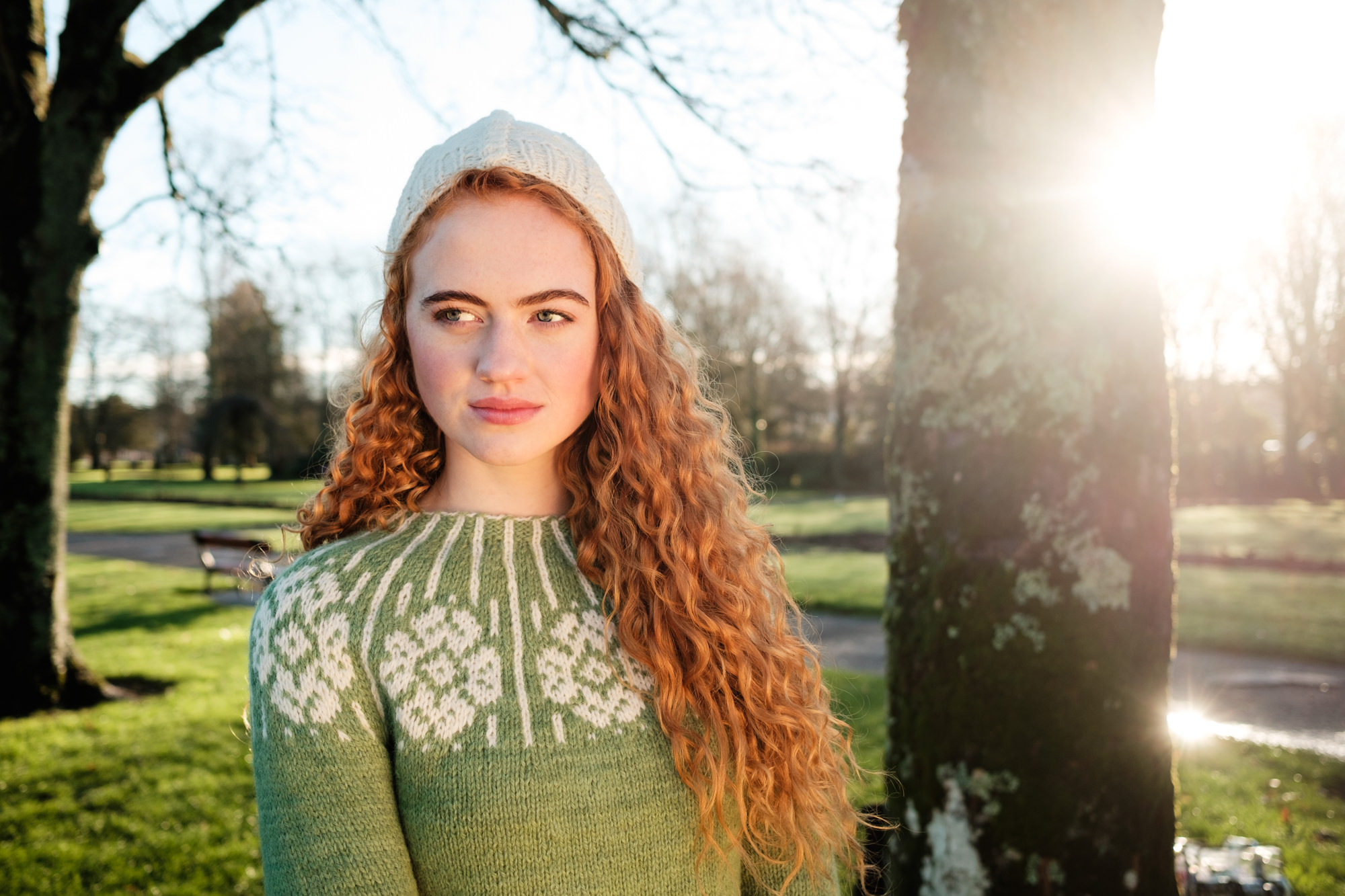 Red haired model wearing 100% Irish knitwear patterned green pullover jumper and cream wooly hat by Rory O'Toole