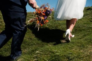bride and groom running across grass