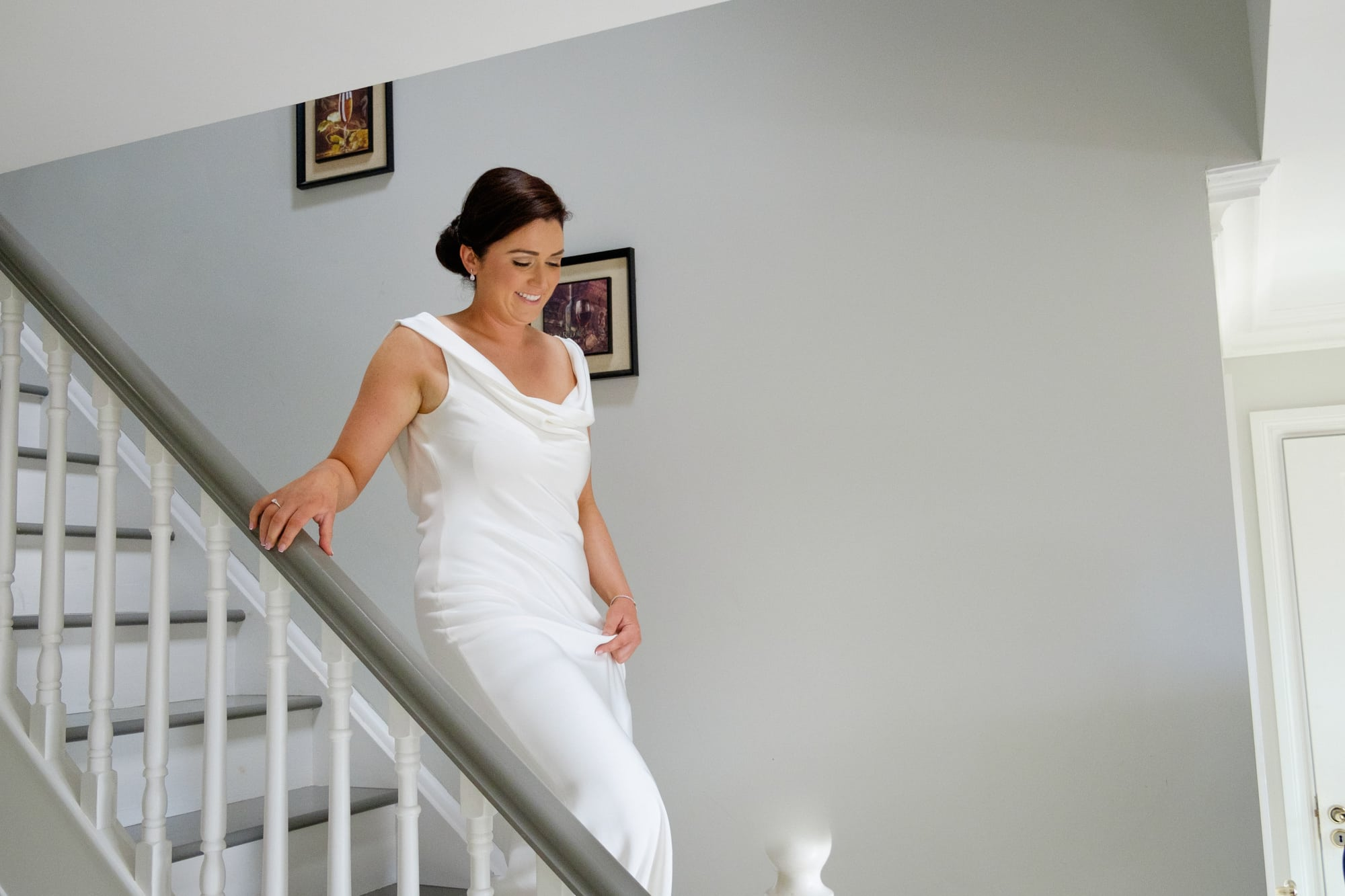 bride coming down hte stairs in her dress to meet father