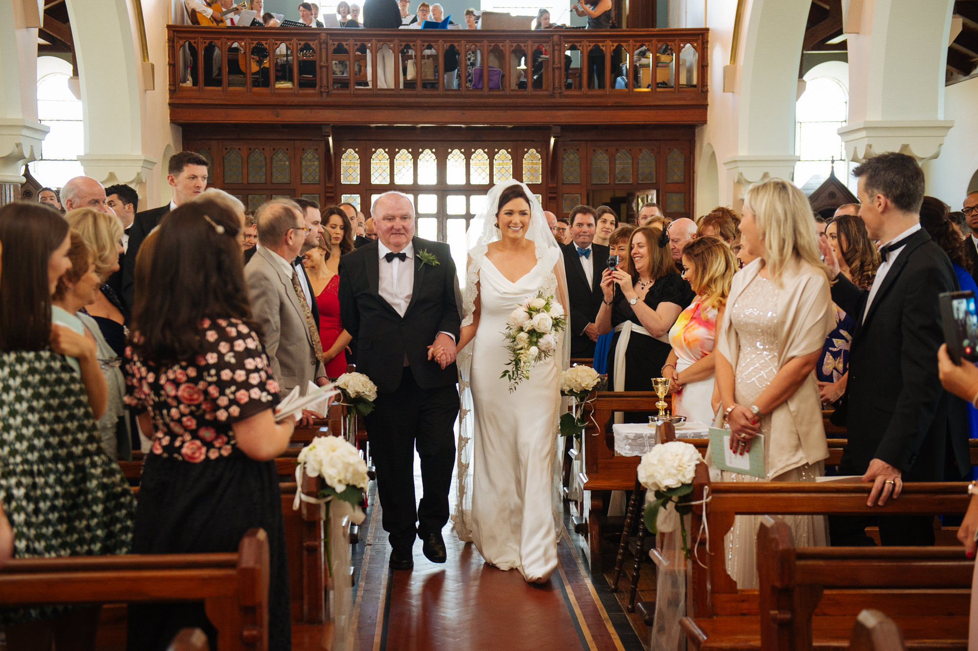 bride walking down the aisle with her father in ballycotton church star of the sea