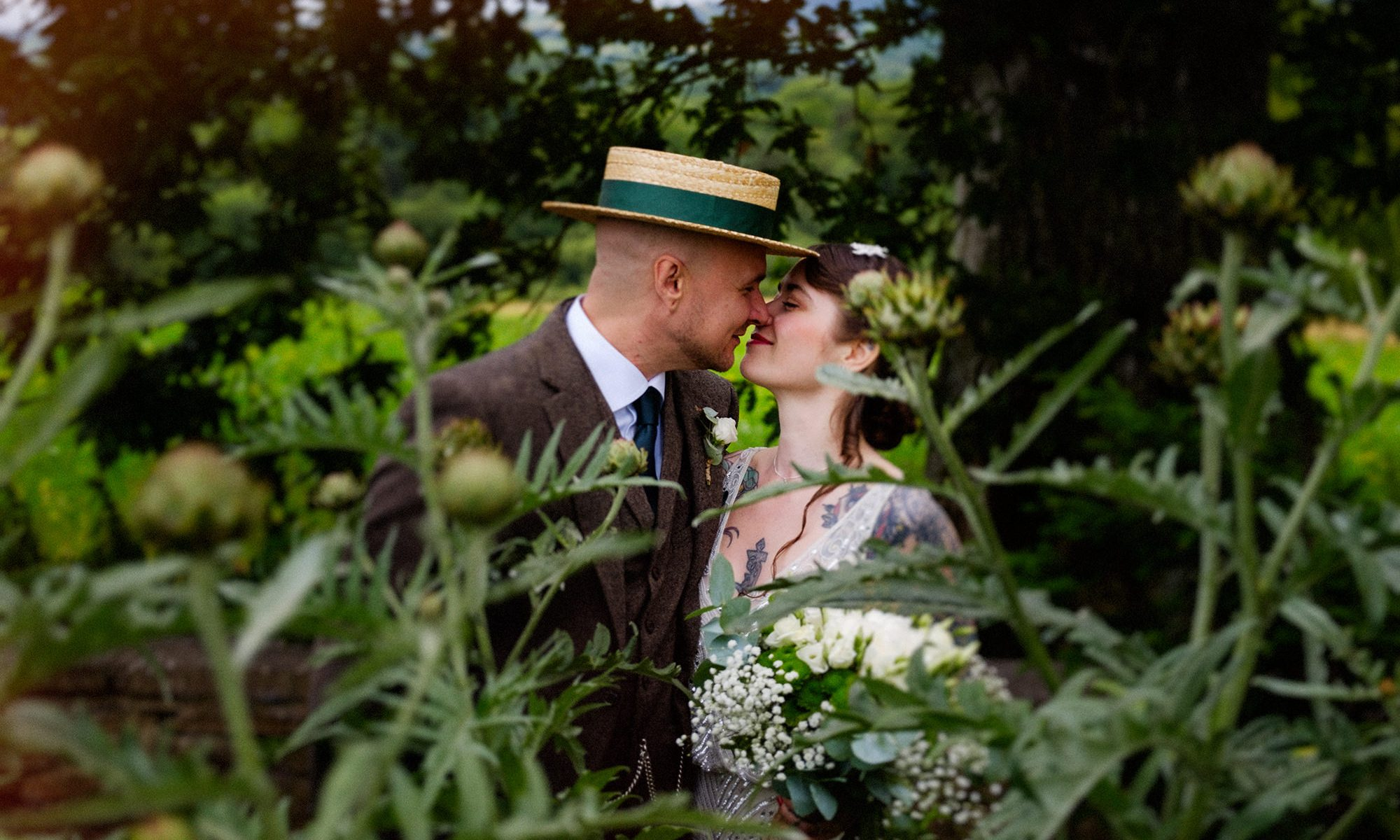 Tattoo bride and groom kiss behind plants